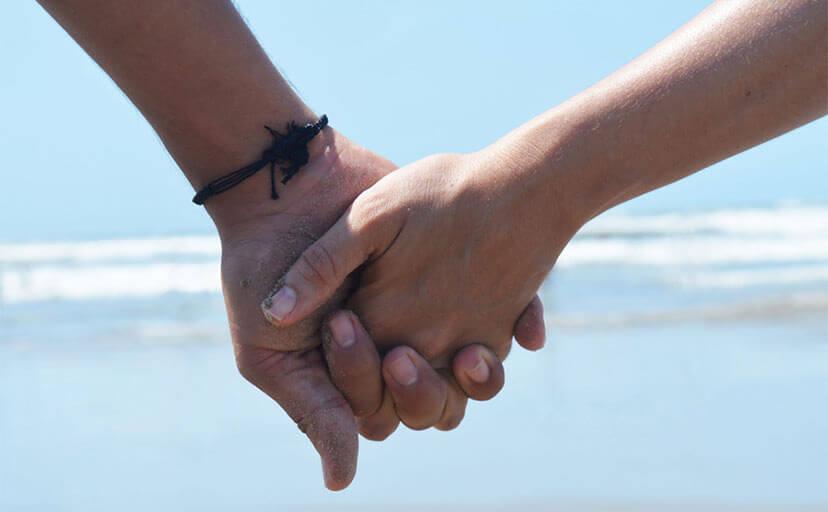 浜辺で手を繋ぐカップル(フリー写真)