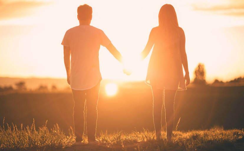 手を繋いで夕日を眺めるカップル(フリー写真)