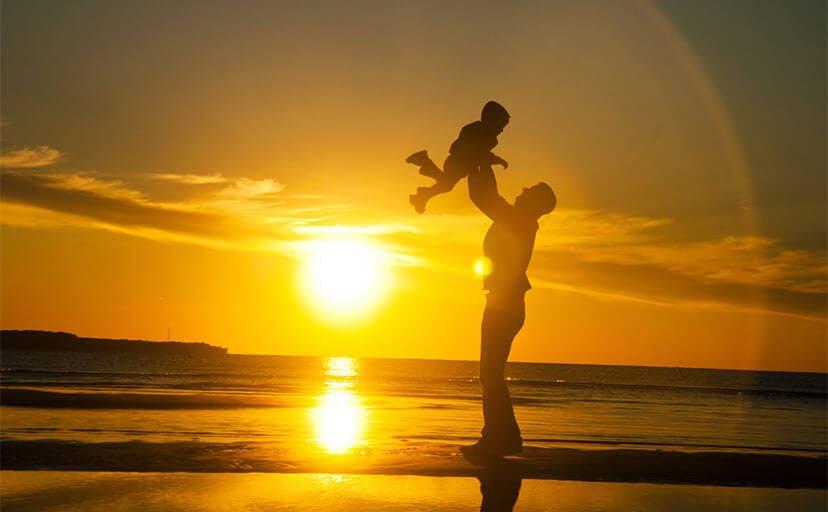 浜辺で子供を抱き上げる父親(フリー写真)