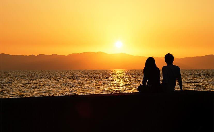 夕日とカップル(フリー写真)