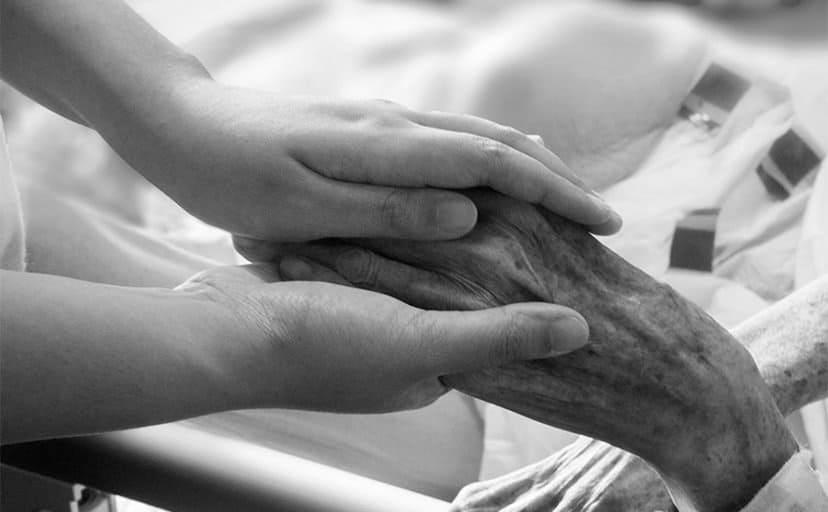 老人の手を握る(フリー写真)